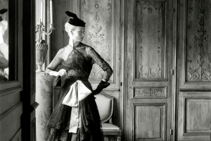 ca. 1951 --- Original caption: Woman modeling black lace dress with pink sash copied from Balenciaga, with hat and gloves. --- Image by © Condé Nast Archive/Corbis
